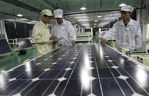 Chinese workers examine solar panels recently at a manufacturer of photovoltaic products in Huaibei in central China's Anhui province.
