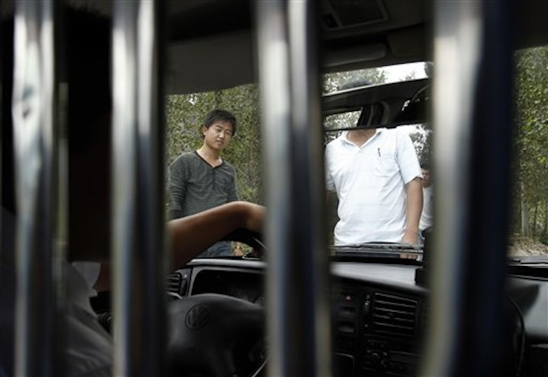 In this Sept. 9, 2010 file photo, unidentified men block a journalist's vehicle from entering Dongshigu Village where blind activist Chen Guangcheng was locked down, in eastern China's Shandong province. While China has long been a police state, controls on these non-offenders mark a new expansion of police resources at a time the authoritarian leadership is consumed with keeping its hold over a fast-changing society. (AP Photo/Andy Wong, File)