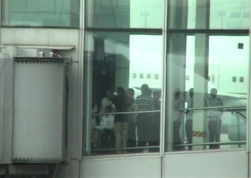 This video image taken from AP video shows blind Chinese activist Chen Guangcheng, left, pushed in a wheelchair from an elevator to a sky bridge that is connected to a plane at Beijing International airport Saturday May 19, 2012. A blind Chinese activist was hurriedly taken from a hospital Saturday and boarded a plane that took off for the United States, closing a nearly monthlong diplomatic tussle that had tested U.S.-China relations. Chen Guangcheng, his wife and their two children were on United Airlines Flight 88, which took off late Saturday afternoon from the Beijing airport. (AP Photo via AP video)