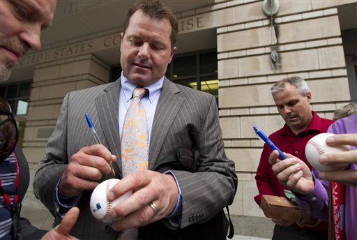 Former Major League Baseball pitcher Roger Clemens autographs baseballs as he leaves the Federal Court in Washington on Wednesday.