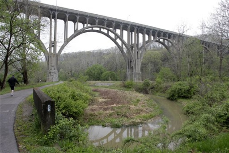 A man walks along the tow path approaching the Station Rd. Bridge at the Cuyahoga Valley National Park in Brecksville, Ohio, Tuesday, May 1, 2012. Five men have been arrested for conspiring to blow up the high level bridge over the Cuyahoga River valley, but there was no danger to the public because the explosives were inoperable and were controlled by an undercover FBI employee, the agency said Tuesday in announcing the men's arrests. (AP Photo/Amy Sancetta)