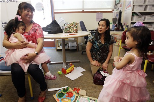 Angelina Sabuco, 2, sleeps in the arms of her aunt Marites Sabuco as her mom Ginady and twin sister Angelica look on at Lucile Packard Children's Hospital on Monday in Palo Alto, Calif.