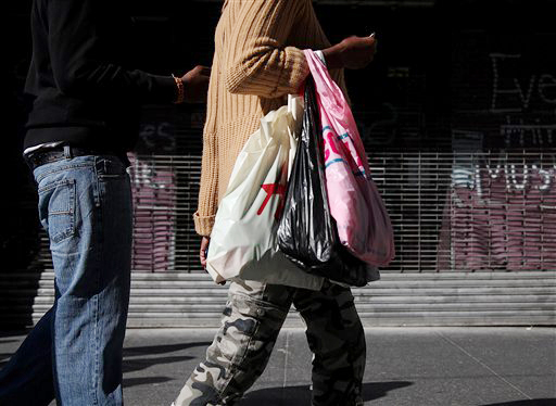 Shoppers carry their purchases along 33rd Street in New York recently. Americans' confidence in the economy in May had its biggest drop in eight months as consumers fretted about slow hiring, a big stock market drop and the global economy, according to the Conference Board, a private research group.