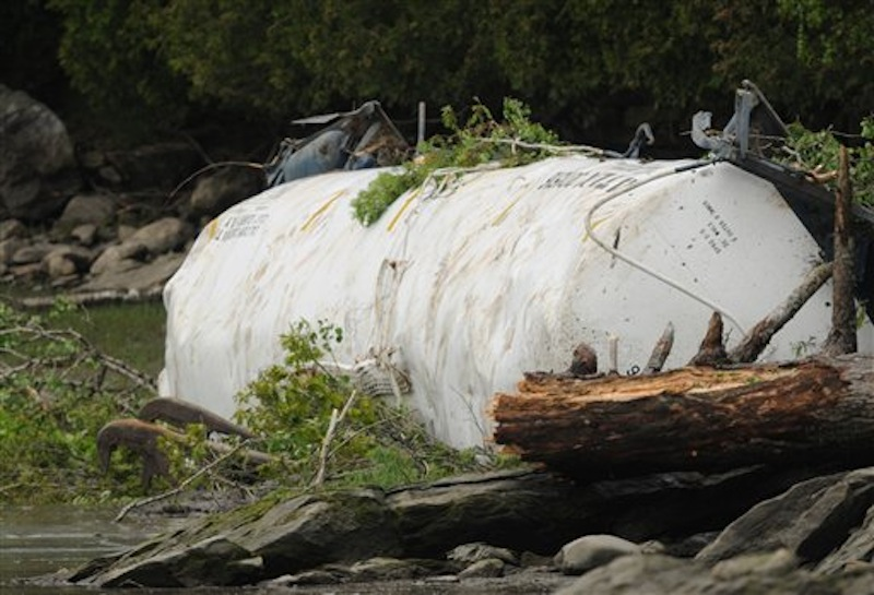 One of two tanker cars is seen along the shoreline of the Penobscot River on Saturday, May 26, 2012 near the Orrington -Bucksport town line after four tanker cars derailed on Friday sending two of the tankers over an embankment and into the Penobscot River. (AP Photo/Bangor Daily News, Kevin Bennett)