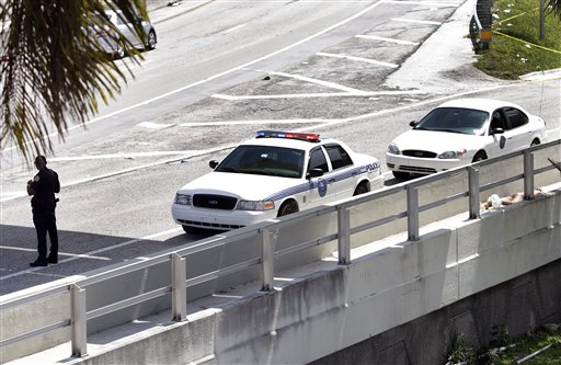 A Miami police officer stands watch near the scene where a man was shot dead in Miami on Saturday. A witness said the man, Rudy Eugene, continued to chew on the face of another naked man and growled when a police officer tried to stop him. The victim remained hospitalized Monday.