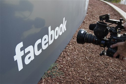 A television camerman shoots the sign outside of Facebook headquarters in Menlo Park, Calif., today.