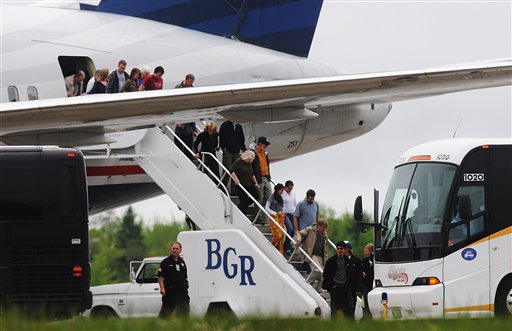 Passengers de-plane a trans-atlantic flight originating in France on the tarmac at Bangor International Airport, in Bangor, Maine, Tuesday, May 22, 2012. Officials briefed on the incident say a French passenger passed a note to a flight attendant saying she had a surgically implanted device. (AP Photo/Bangor Daily News, Kevin Bennett)