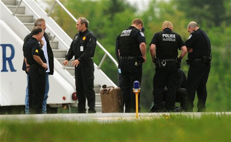 Law enforcement officials stand near a jet bridge next to a passenger jet on the tarmac at Bangor International Airport, in Bangor, Me., Tuesday, May 22, 2012. The plane was diverted to Maine during its flight from France to Charlotte. Officials briefed on the incident say a French passenger passed a note to a flight attendant saying she had a surgically implanted device. (AP Photo/Bangor Daily News, Kevin Bennett)