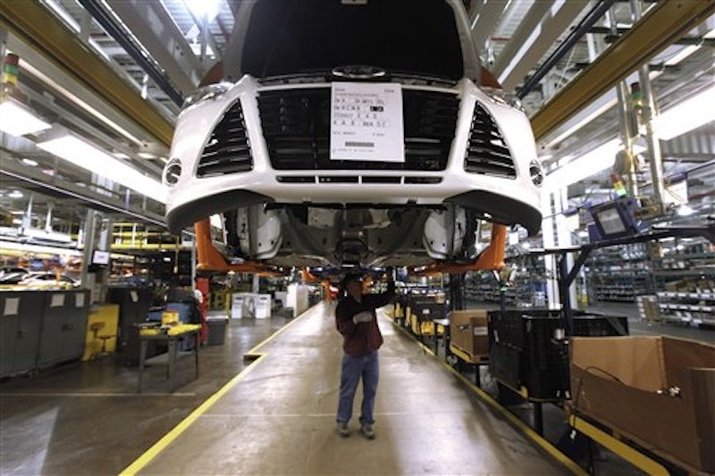 In this Dec. 14, 2011 file photo, a line worker assembles a 2012 Ford Focus at the Ford Michigan Assembly plant in Wayne, Mich. The plant is one 13 North American factories where Ford Motor Co. will be adding a a week of production in 2012, so the company can make another 40,000 vehicles this year and meet the needs of rising car and truck sales. (AP Photo/Paul Sancya, File)