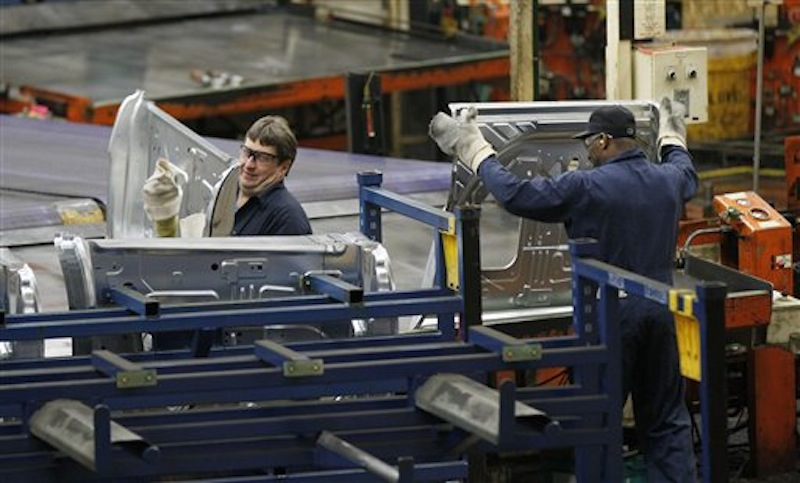 In this April 4, 2012 file photo, auto workers at the Ford Stamping Plant in Chicago Heights, Ill., stack the inner door panel for a Ford Explorer. On Tuesday, May 8, 2012, Ford said it will make 40,000 additional cars and trucks this year by cutting a week out of the normal summer shutdown at 13 factories. Auto plants normally close for two weeks around the July 4 holiday to switch production to the next model year. But Ford says the plants will close for only one week in order to keep up with rising demand for Ford vehicles. (AP Photo/Charles Rex Arbogast, File)