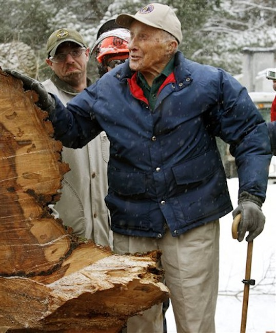 """In this Jan. 19, 2010 file photo, Frank Knight puts his hand on New Englandís tallest elm tree, known as """"Herbie,"""" after it succumbed to Dutch elm disease and was cut down in Yarmouth, Maine. Knight, who took care of the tree for five decades while working as the Yarmouth tree warden, died in Scarborough, Maine, Monday, May 14, 2012. He was 103. (AP Photo/Pat Wellenbach, File)"""