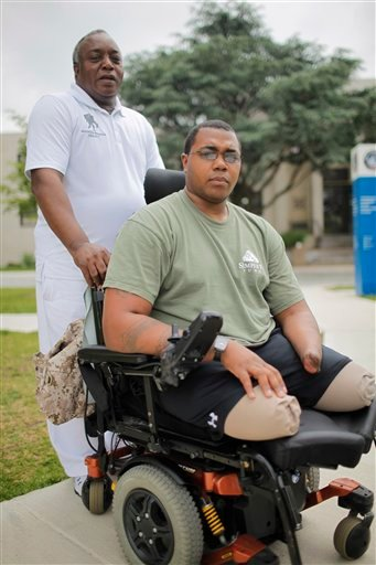 Larry Bailey, left, stands with his son Marine Cpl. Larry Bailey II of Zion, Ill., at Walter Reed National Military Medical Center in Bethesda, Md., last week. The 26-year-old Marine tripped a rooftop bomb in Afghanistan in June 2011. He ended up a triple amputee and expects to get a hand transplant this summer.