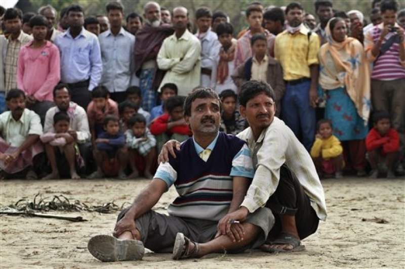 Abdul Mazid, 42, center, whose sister is missing anxiously watches rescuers pull out the wreckage of a ferry that capsized in the Brahmaputra River at Buraburi village, about 350 kilometers (215 miles) west of the state capital Gauhati, India, Tuesday, May 1, 2012. Army divers and rescue workers pulled more than 100 bodies out of a river after a packed ferry capsized in heavy winds and rain in remote northeast India, an official said Tuesday. At least 100 people were still missing Tuesday after the ferry carrying about 350 people broke into two pieces late Monday, said Pritam Saikia, the district magistrate of Goalpara district. (AP Photo/Anupam Nath)