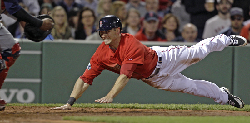 Boston's Daniel Nava dives into home plate to score on a hit by Cody Ross in the fifth inning against the Cleveland Indians at Fenway Park in Boston on Friday.