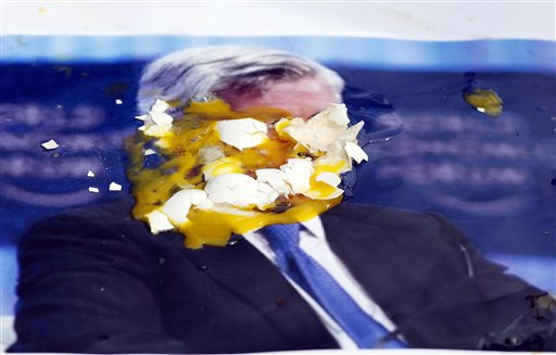 A poster of JPMorgan Chase CEO Jamie Dimon is covered with eggs thrown by protesters, outside the gate of JP Morgan Chase annual stockholders meeting today in Tampa, Fla.