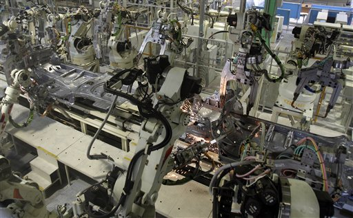 In this Feb. 16, 2011 file photo, robots make Yaris compact sedans on a newly opened assembly line at a plant of Toyota Motor Co.'s group company Central Motor Co. in Ohira in Miyagi Prefecture, northern Japan. Canon Inc. is moving toward fully automating digital camera production in an effort to cut costs - a key change being played out across Japan, a world leader in robotics. If successful, counting on machines can help preserve this nation's technological power - not the stereotype of machines snatching assembly line jobs from workers, Jun Misumi - company spokesman, said Monday, May 14, 2012. (AP Photo/Koji Sasahara, File)