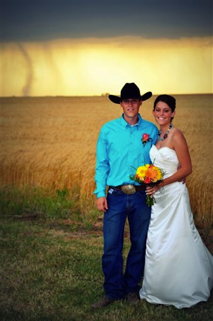 In this May 19, 2012, photo provided by Cate Eighmey, Caleb & Candra Pence pose for a wedding photo as a tornado swirls in the background after they were married in Harper County, Kan. (AP Photo/Cate Eighmey)