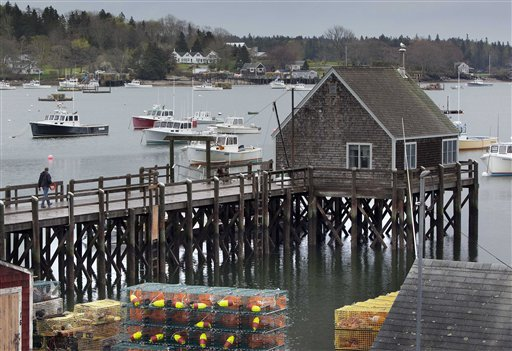 A man walks out on a wharf in Friendship's postcard-pretty harbor, where two sabotaged lobster boats were cut free and allowed to flood with water.
