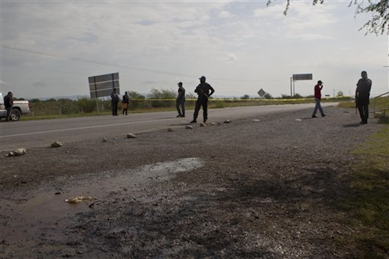 Federal police guard as forensic experts examine the area where dozens of bodies, some of them mutilated, were found on a highway connecting the northern Mexican metropolis of Monterrey to the U.S. border in the town of San Juan near the city of Monterrey, Mexico, Sunday, May 13, 2012. (AP Photo/Christian Palma)