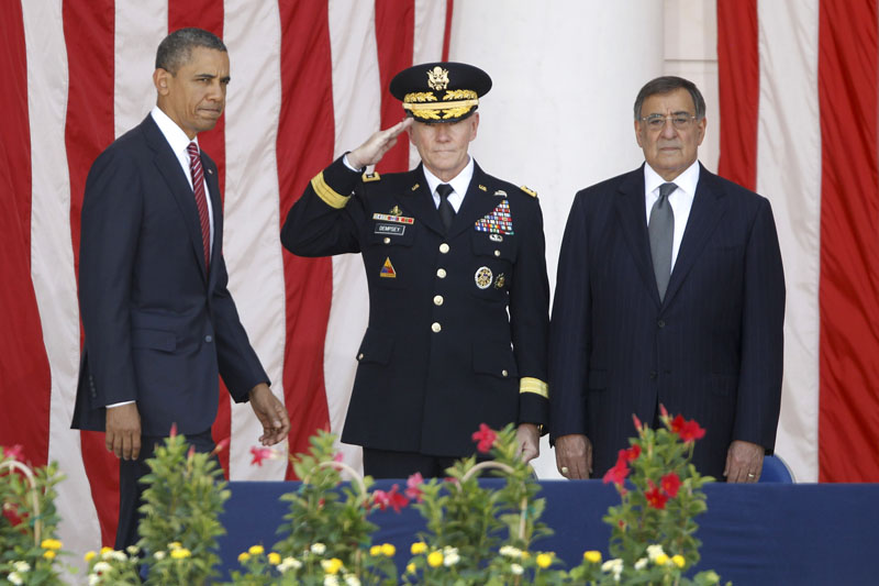 President Barack Obama arrives on stage at the Memorial Day Observance at the Memorial Amphitheater at Arlington National Cemetery, Monday, May 28, 2012. At center is Chairman of the Joint Chiefs of Staff Gen. Martin Dempsey and Defense Secretary Leon Panetta is at right.