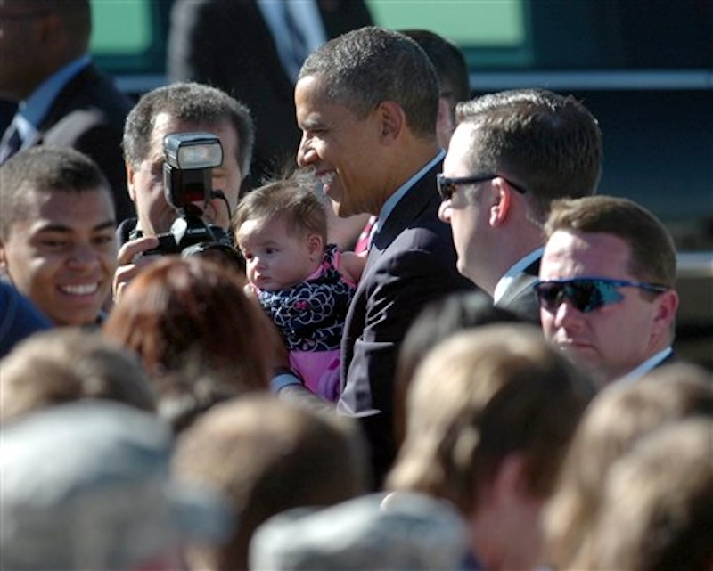 President Barack Obama holds a young child and talks with a crowd upon his arrival at Peterson Air Force Base, Colo., Wednesday, May 23, 2012. Obama will deliver the commencement speech to the Air Force Academy graduates. (AP Photo/Bryan Oller) Bryan Oller;Obama;Air Force Academy;Graduation;Air Force One;Peterson;Colorado Springs