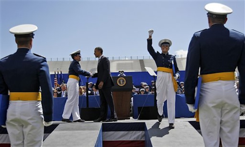 "A cadet celebrates after being congratulated by President Barack Obama, center, during graduation ceremonies for the 2012 class of the U.S. Air Force Academy, Wednesday, May 23, 2012, in Colorado Springs, Colo. Government spending and debt are emerging as a campaign tug-of-war. Republican Mitt Romney blames President Barack Obama for a ""prairie fire of debt."" Obama calls the charge a ""cowpie of distortion."" Both candidates are reaching for unaligned, independent voters anxious about who's going to get stuck with the bill. (AP Photo/Pablo Martinez Monsivais)"