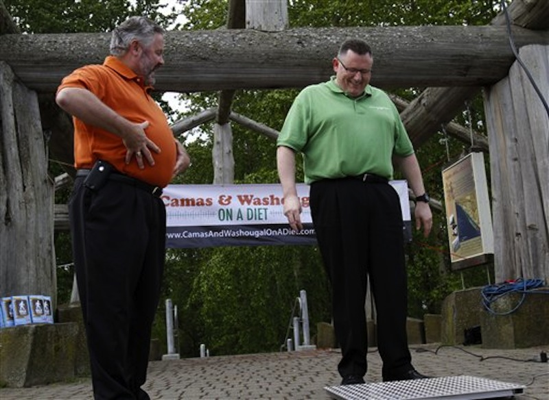 In this May 2, 2012 file photo, Washougal Mayor Sean Guard, left, coaxes Camas Mayor Scott Higgins to step on the scales during their weigh-in in Washougal, Wash. The mayors of the two neighboring towns are in a