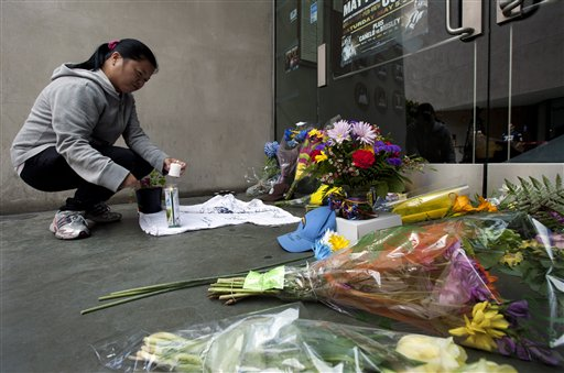 Gemma Estenol lights a candle to leave in front of the doors of former NFL football player Junior Seau's restaurant on Wednesday in San Diego.
