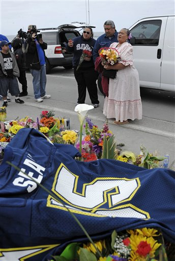 Family members of former NFL star Junior Seau put flowers at a memorial in the driveway of his home on Thursday in Oceanside, Calif.