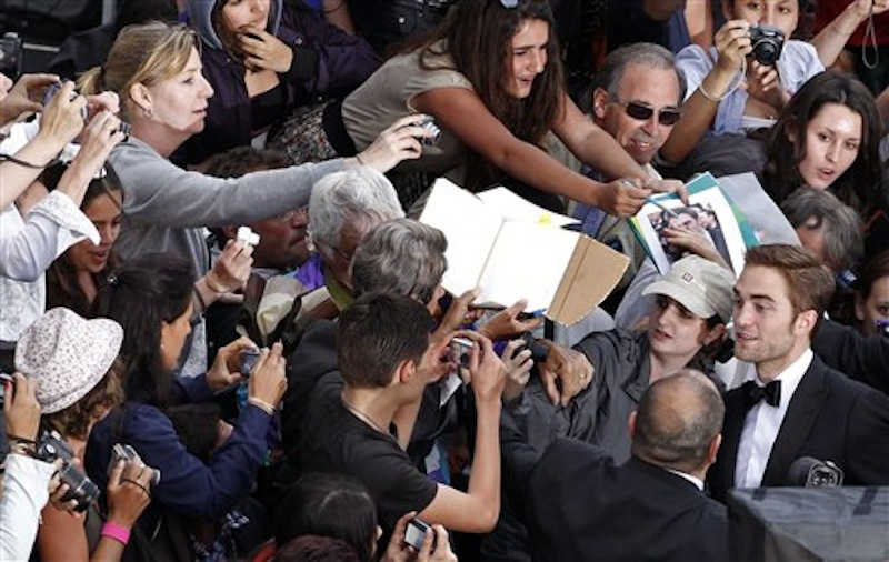 Actor Robert Pattinson, foreground right, greets fans as he arrives for the screening of Cosmopolis at the 65th international film festival, in Cannes, southern France, Friday, May 25, 2012. (AP Photo/Vincent Kessler, Pool)