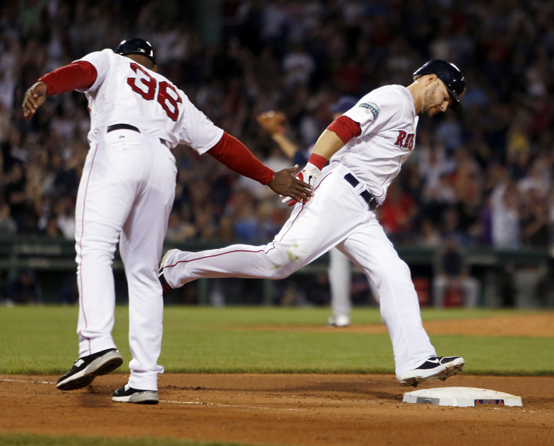 Red Sox first base coach Alex Ochoa reaches out to Cody Ross as he rounds the bases on a solo home run in the sixth inning Saturday.
