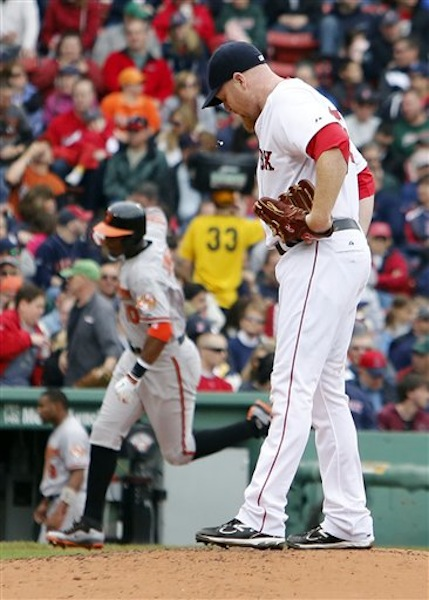 Boston Red Sox starting pitcher Aaron Cook looks down after giving up a two-run home run to Baltimore Orioles' Adam Jones, background left, during the third inning of a baseball game in Boston, Saturday, May 5, 2012. (AP Photo/Michael Dwyer)