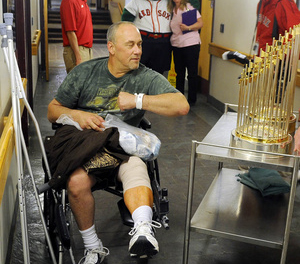 TROPHY ENCOUNTER: Mark Allen, of West Gardiner, brushes up against the Boston Red Sox 2004 and 2007 World Series trophies following knee surgery Wednesday at VA Maine Healthcare System-Togus. The Fenway Ambassadors visited patients and supporters of the health care facility for veterans.