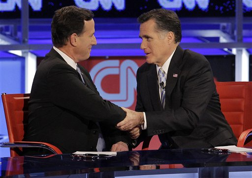 Republican presidential candidate Mitt Romney, right, talks with former Pennsylvania Sen. Rick Santorum after a presidential debate in Arizona in this Feb. 22, 2012, photo.