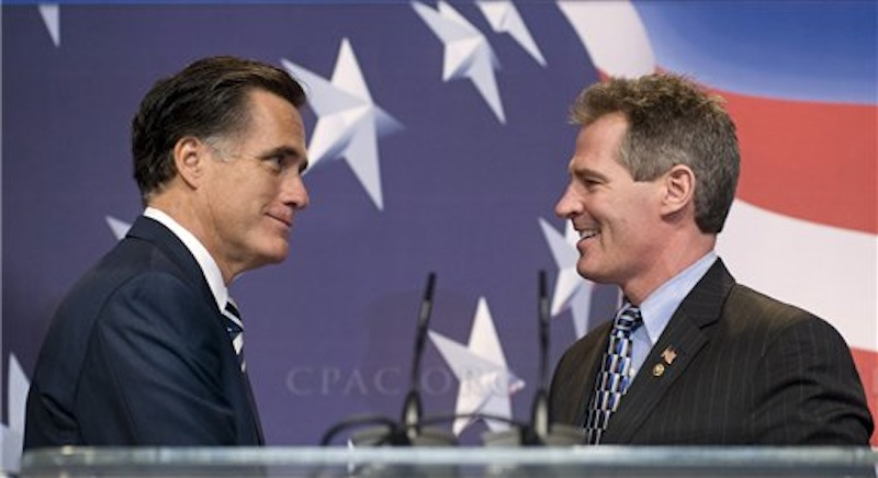 In this Feb. 18, 2010, file photo former Massachusetts Gov. Mitt Romney, left, is announced by Sen. Scott Brown, R, Mass., as he arrives on stage to speak at the Conservative Political Action Conference in Washington. The two Massachusetts Republicans have a history of supporting each other throughout their political careers, but facing tough elections neither is the presidential candidate nor the U.S. senator is playing up that history now, perhaps with good reason. (AP Photo/Cliff Owen, File)