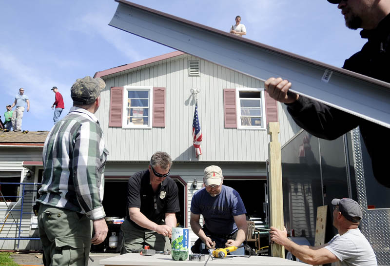 Staff photo by Andy Molloy GOING UP: Game Wardens and friends of Warden Service Major Gregg Sanborn put a new roof on his Sidney home Monday. Sanborn, who is afflicted with cancer, said about 25 of his colleagues and friends simply
