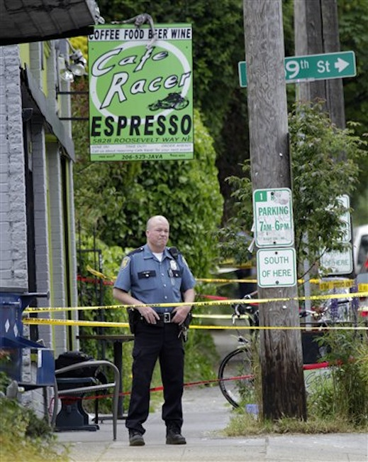 A Seattle Police officer stands outside a cafe where a shooting took place, Wednesday, May 30, 2012. A gunman opened fire at the cafe in Seattleís University district Wednesday, killing two people and critically wounding three others. Police are searching for the gunman, described as a man in his 30s wearing dark clothes. (AP Photo/Ted S. Warren)