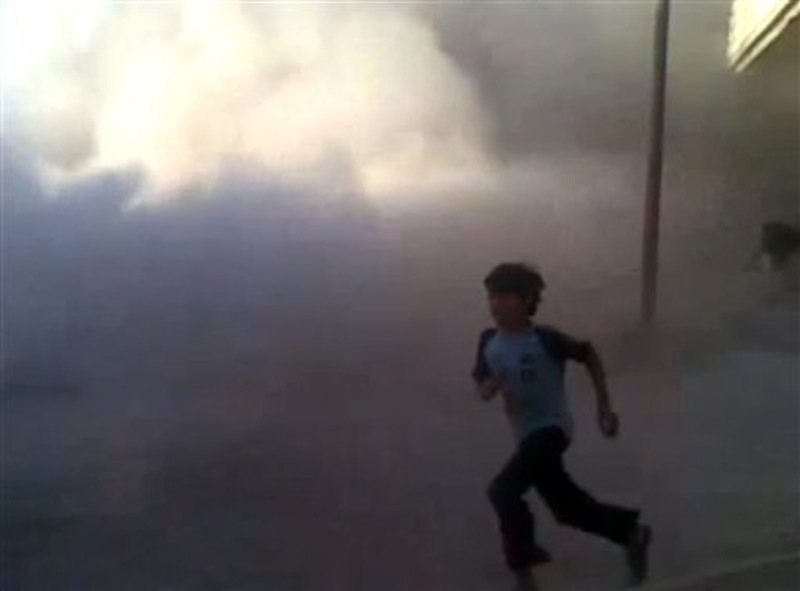 This frame grab made from an amateur video provided by Syrian activists on Monday, May 28, 2012, purports to show the massacre in Houla on May 25 that killed more than 100 people, many of them children. The amateur footage shows people running along a street, purportedly just after the attack on Houla started. (AP Photo/Amateur Video via AP video)