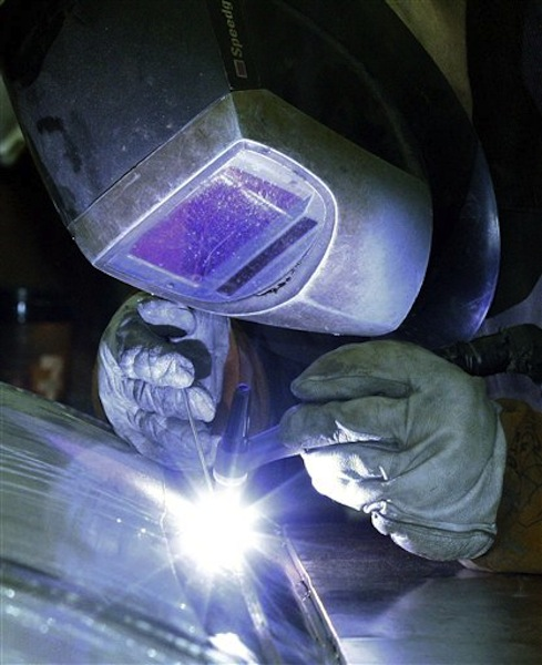 In this Feb. 13, 2012 file photo, a workman welds a stainless steel tank at JV Northwest, in Camby, Ore. JV Northwest manufactures stainless steel vessels. U.S. factories stepped up hiring and production in March, the latest evidence that manufacturing is growing at a healthy pace and fueling the recovery. (AP Photo/Rick Bowmer, File)