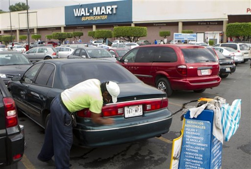 In this Saturday, April 21, 2012 photo, a man cleans a car in the parking outside a Walt-Mart Super Center. Wal-Mart will install solar panels at all its Massachusetts stores within the next two years. (AP Photo)