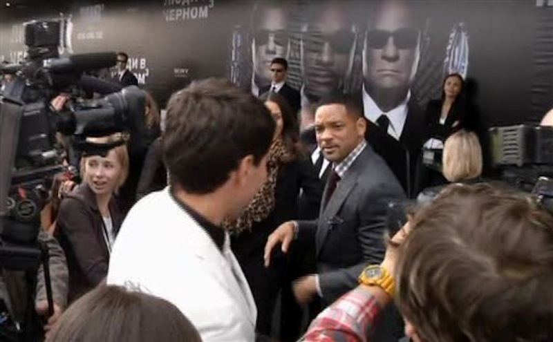 In this video image taken from AP video U.S. actor Will Smith, center right, walks away from reporter Vitalii Sediuk, white suit, from the Ukrainian television channel 1+1 after slapping him on the red carpet before the premiere of