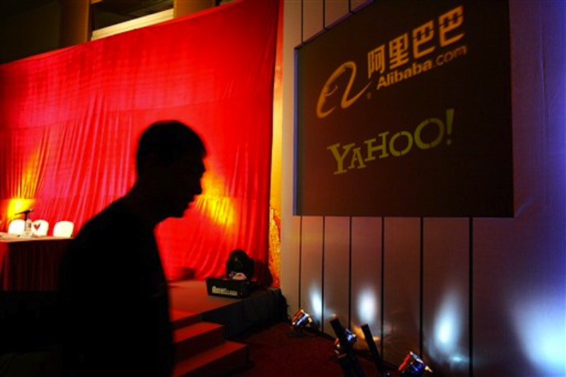 In this Aug. 11, 2005, file photo, a man walks past a screen displaying the Yahoo and Ali Baba.com logos before a joint news conference by the companies at the China World hotel in Beijing. Yahoo announced that it has agreed to sell half of its 40 percent stake in Chinese e-commerce company Alibaba for about $7.1 billion. The deal will see Alibaba Group buying back the stake from Yahoo Inc. for $6.3 billion cash and up to $800 million of Alibaba preference shares. (AP Photo/Elizabeth Dalziel, File)