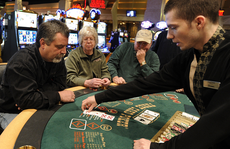 Shawn Hollobaugh, right, deals cards to Tom Gagne of Bangor, left, as others watch during a game of three card poker at the Hollywood Casino in Bangor in this March 16 photo. When compared with 2010 figures, Maine's gross gaming revenue dropped by 3.6 percent in 2011. and its gaming tax receipts fell by 3.7 percent year-over-year.