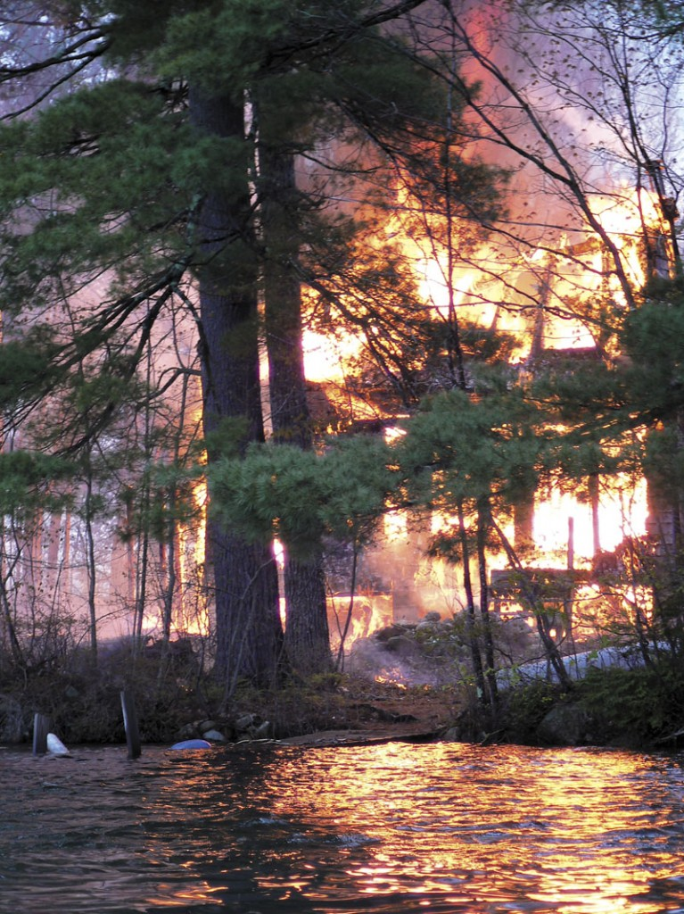 Smoke rises from a house fire on an island in Togus Pond on Friday. A 15-year-old boy has been charged with setting the fire and burglarizing other homes on Coon Island.
