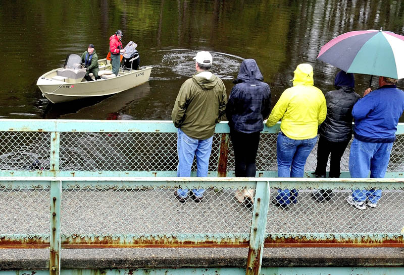 WAIT AND WATCH: Family members of missing driver Cora Marley watch as game wardens in a boat and divers search Martin Stream in Hinckley on Tuesday at the site where Marley's vehicle struck a bridge and sank last Saturday.