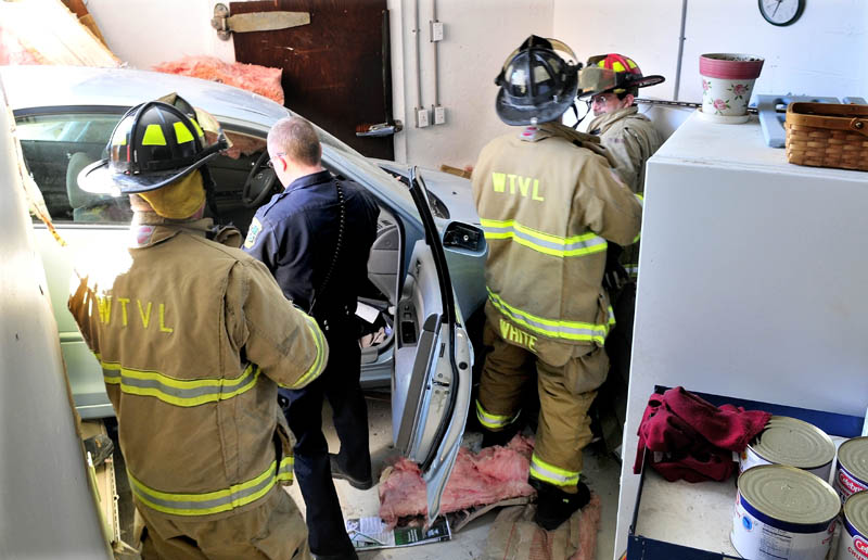 SURPRISE ENTRY: Waterville police officer Adam Sirois and firefighters work around the vehicle that crashed into the Darrell's Pizza business in Waterville on Monday. Driver Sharon Roderick of Fairfield escaped with minor injuries.