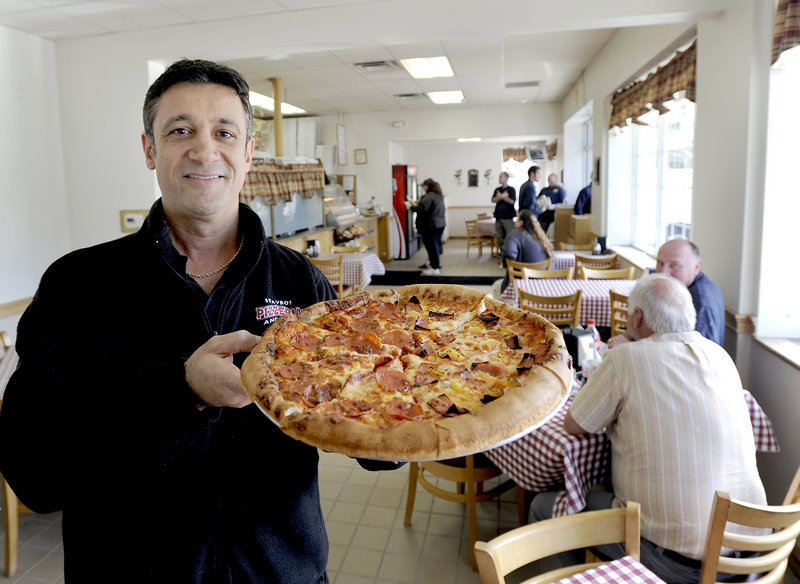 Steve Kombakis, owner of Stavros Pizzeria and Deli in Portland, shows off a half-pepperoni, half-Hawaiian pizza.