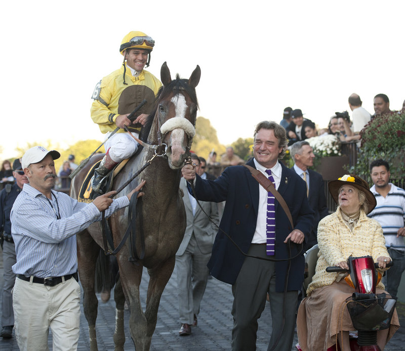 Jamie Wyeth, wearing the purple tie, leads Union Rags down victory lane at Belmont Park after the Champagne Stakes in October 2011. At right is his wife and the horse's owner, Phyllis, operator of Chadds Ford Stable in Pennsylvania.