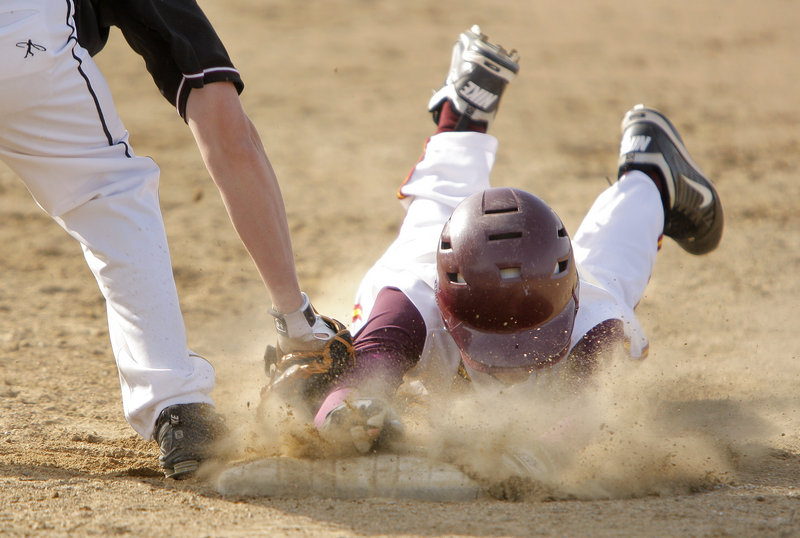Connor Maguire of Cape Elizabeth gets a face full of dirt as he dives back to first ahead of the tag by Greely's Luke Saffian in Monday's game at Cumberland. Greely won, 8-0.
