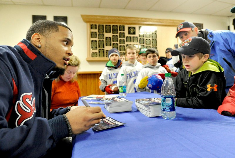 Patriots safety Patrick Chung chats with Connor DeCoster, 6, and his dad, Jay DeCoster, from Turner during his visit to Hadlock Field Tuesday night.